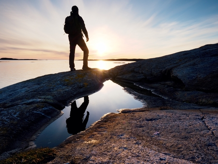 Hiker in dark sportswear with poles and sporty backpack. Coastline trail on rocky shore. Alone tourist enjoy magic end of day with amazing view to horizone. Stock Photo