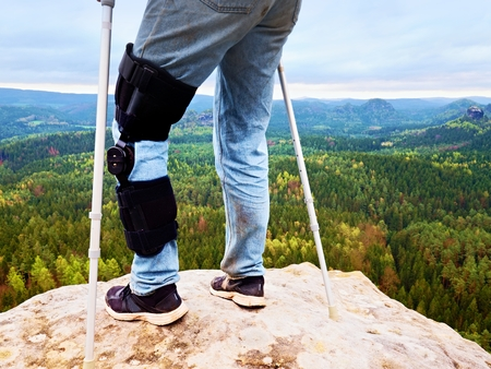 Close Up Of Man Walking With Crutches  in nature. Man legs in jeans with adjustable Bandage on pain knee.