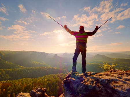 Hiker with hurts knee. Man with leg in join immobilizer stay on summit and raise medicine crutch above head. Hiker achieved mountain peak within surmount pain. Stock Photo