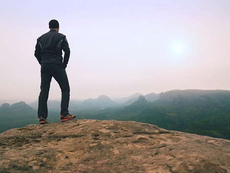 Nature hiker on sharp cliff roc watching over misty  valley to blurred horizon. Terrible rainy weather with thick fog. Man alone thinking with hands in pocket.