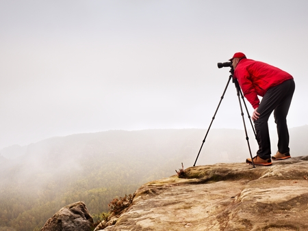 Hiker with camera on tripod takes picture from rocky summit. Alone photographer at edge stock photography misty landscape, forest in the valley. Stock Photo