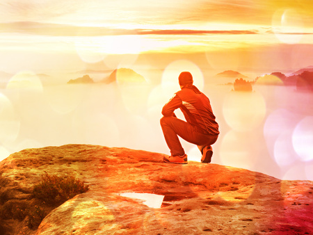 Lens defective. Tourist sit on a sandstone rock and watch in a colorful mist and fog in the morning valley. Sad man. Man sit. Man in jeans.Fall mountain mist. Mist in the valleys.