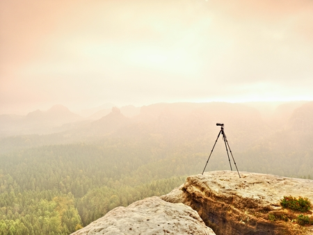 Tripod on the top ready for photogrpahy. Exposed rocky view point. Misty rainy autumn day in wild nature. Stock Photo