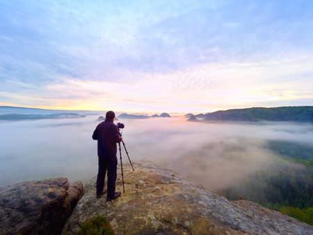 picture framing: Photographer framing picture with eye on viewfinder. Photo enthusiast  enjoy work of fall nature on rocky summit. Dreamy landscape, misty sunrise in a beautiful valley below