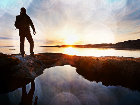 Lens defect.  Tall backpacker watch clear sunny spring daybreak over sea. Hiker with backpack stand on rocky shore and his figure is mirrored in water pool. Reklamní fotografie