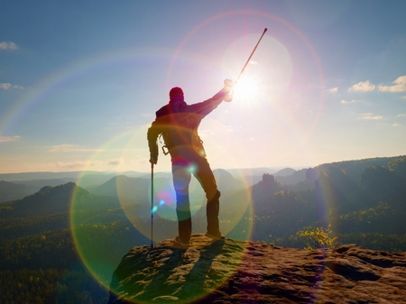 Tourist with  forearm crutch above head  on trail. Hurt hiker achieved mountain peak with broken knee in immobilizer.  Deep valley bellow silhouette of man. Early autumnal daybreak Stock Photo
