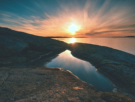 Beautiful seascape view. The mirroring of  sunsetting horizon in water pools in the rocks . Smooth ocean with light blue sky and blured clouds. The sun shine golden light and reflect on water and flare.