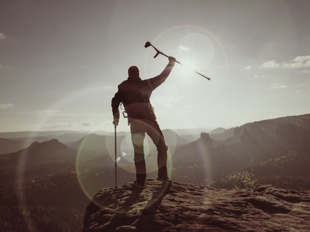 Tourist with medicine crutch above head achieve mountain peak. Hurt backpacker with broken leg in immobilizer stay above valley . The silhouette of man with hand in air