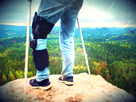 Lens defect. Man tourist wearing a knee brace with adjustable side panels to immobilize and support hurt leg. Man walking againts the crutches outdoors on hike trip