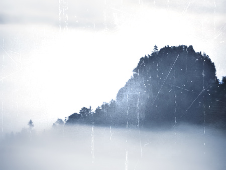 Lens defective. View into the misty valley. High trees and rocky peaks have increased from thick fog. The first sun rays create sharp outlines in the mist. Stock Photo