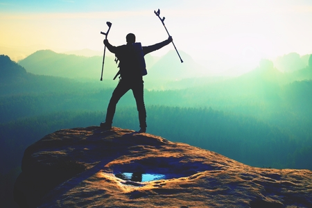 Tourist with  medicine crutch above head achieved mountain peak. Hiker with broken leg in immobilizer.  Deep misty valley bellow silhouette of man with hand in air. Spring daybreak Stockfoto
