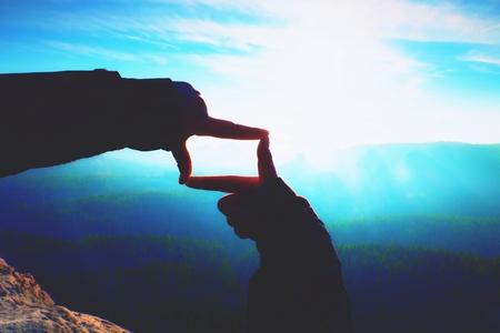 間近で手は、フレーム消すジェスチャを行います。青い霧谷怒鳴る岩が多い峰。山地の日当たりの良い春の夜明け。 写真素材