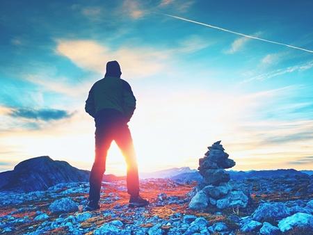 zvýšil: Stones pyramid on Alpine gravel mountain summit. Daybreak horizon above blue mist in valley. Mountains increased from horizoon Reklamní fotografie