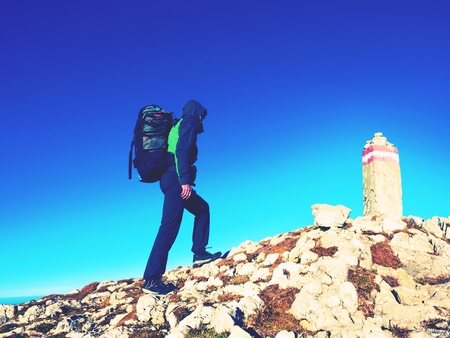 range hood: Hiker with backpack climbing on mountain peak. Stone Summit at Alps mountain top. Tourist walk with heavy backpack Stock Photo