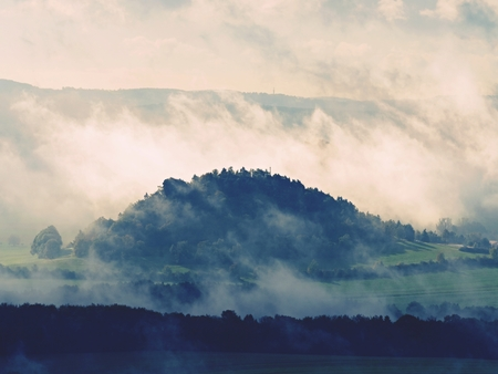 Distant mountain range and heavy clouds of colorful  mist above deep valleys. Early autumnal day in nature park