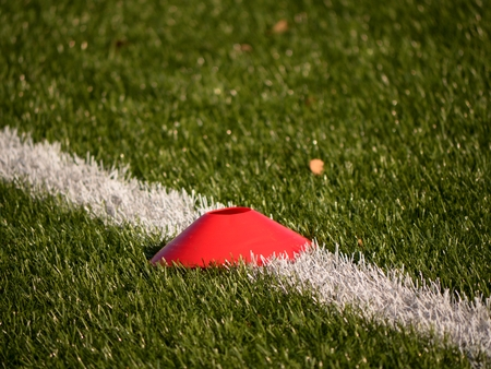 Bright red plastic cone on painted white line of soccer field. Plastic football green turf playground with grind black rubber in core. Stock Photo