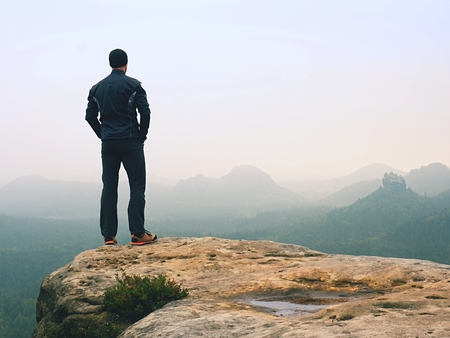 Hiker in sportswear stand on the peak of sandstone rock in rock empires park and watching over the autumnal colorful valley to Sun. Beautiful colors, the  miracle of nature Stock Photo