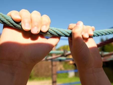 Children hands hold a plastic Climbing Rope In A Outdoor Playground, kids game Stock Photo