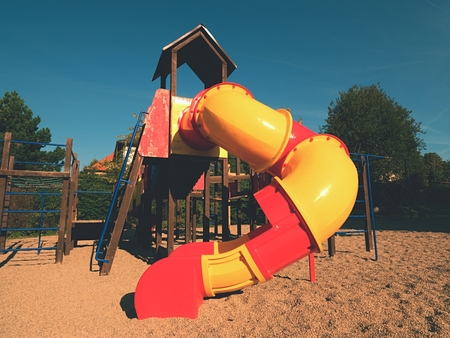 Playground colorful tube slide in public park. New plastic slider tube and wooden ladders Stock Photo
