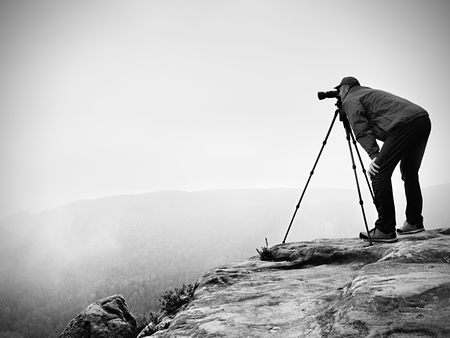 picture framing: Wildlife photographer on mountain summit works. Man like to travel and photography, taking pictures of moments during autumnal sunset in landscape Stock Photo