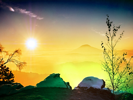 Flare, soft focus. Fantastic dreamy sunset on top of rocky mountain with view into evening autumnal valley. Mountain view Stock Photo