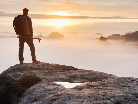 Tired hiker with sporty backpack on rocky peak  and watching into deep misty valley bellow. Sunny spring daybreak in rocky mountains.