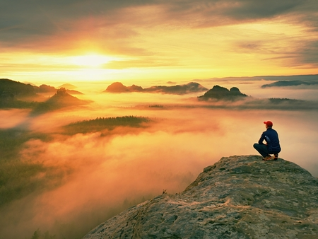 strip shirt: Alone hiker in the red cap standing on the peak of sandstone rock in the rock empire park and watching over the misty and foggy morning valley to Sun. Beautiful moment the miracle of nature