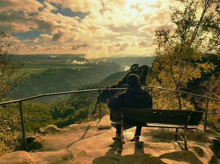 Man hiker at handrail on the peak of sandstone rock watching into misty landscape bellow