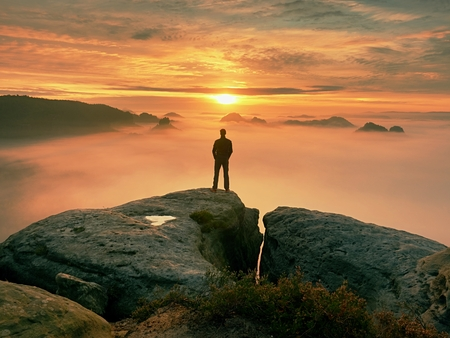 Man stands alone on the peak of rock. Hiker watching to autumn  Sun at horizon . Beautiful moment the miracle of nature. Colorful mist in valley. Man hike. Person silhouette stand