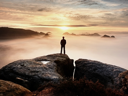 Mannschattenbildaufenthalt auf scharfer Felsenspitze. Befriedigen Sie Wanderer, genießen Sie Ansicht. Großer Mann auf der felsigen Klippe, die unten auf Landschaft aufpasst. Lebendiger und starker Effekt.