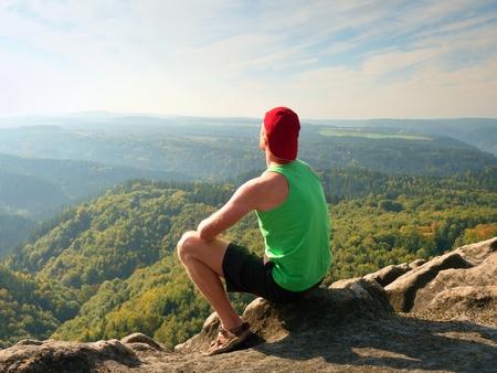 Touriste en maillot de bain vert et short noir sur un rocher, profitez du paysage nature printanier. Longue vallée au bain de soleil pleine de brouillard crémeux