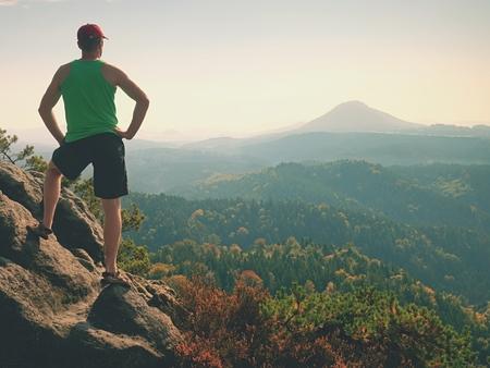Tortue en singulet vert et short noir sur un rocher, profitez des paysages printaniers de la nature. Longue vallée en bain de soleil plein de brouillard crémeux