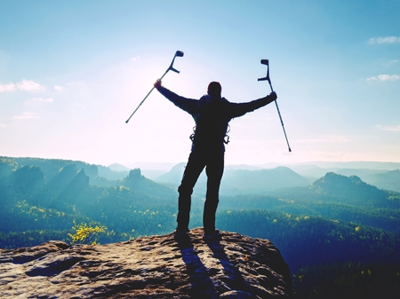 Difficult exam. Man walking againts the crutches outdoors on hike trip Man tourist wearing knee brace with adjustable side panels to immobilize and support hurt leg.