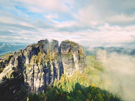 inversion: The thick fog is swinging between rocks and stripes over high trees in spruce forest. Fairy daybreak in silent rocks. Autumn in landscape Stock Photo