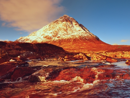 Sunny winter morning at the frozen river Coupall at the delta to the river Etive. Higland in Scotland a marvelous day. Snowy cone of mountain Stob Dearg 1021 meters high. Dry grass and heather bushes on banks. Stock Photo