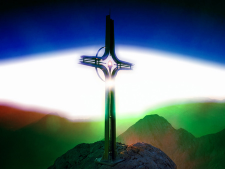 Flare, soft focus. Cross raised  at mountain summit. Sharp peak, daybreak Sun in sky. Steel crucifix in memory of victims of mountains