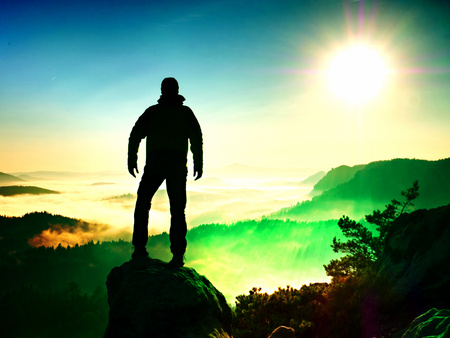 Flare, soft focus. The man standing high on cliff. Stock Photo