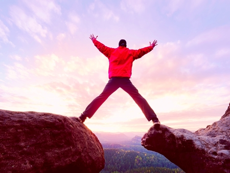 Man jumping from the mountain edge.  Man jumping off a cliff without rope. Risky moment. Rough rocky ground.