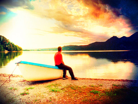 Flare, soft focus. Tiired man in red shirt sit on old fishing paddle boat at mountains lake coast. Vintage photo effect Stock Photo