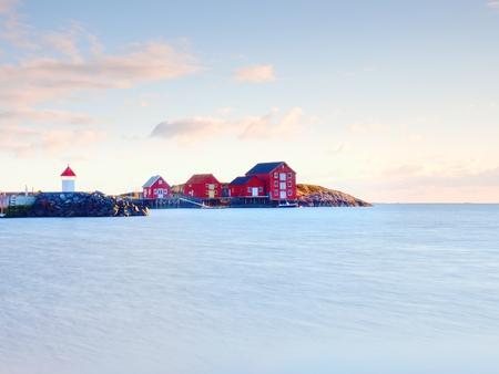 Rode huizen van het vissersdorp. Rode witte gebouwen en vuurtoren in kleine haven, kustlijn van koude Noordzee, Noorwegen.