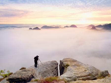 写真フレーム画像ファインダーに目。写真愛好家は、岩の頂上に秋の自然の仕事を楽しみます。夢のような風景、美しい渓谷の下で霧日の出 写真素材