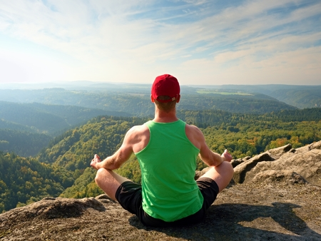Slim body hiker in green singlet and black shorts sit on a rock, enjoy natural scenery. View into forest valley with hills at horizon.