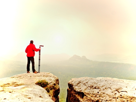 Photographer think about picture on peak  in the misty mountains. Photograph at daybreak above valley hidden in heavy mist.  Landscape view of misty autumn mountain hills and hiker silhouette