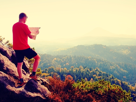 Man in t-shirt and pants on mountain top watching into opened landscape and check the map. Rainforest valley up to horizon. Banco de Imagens