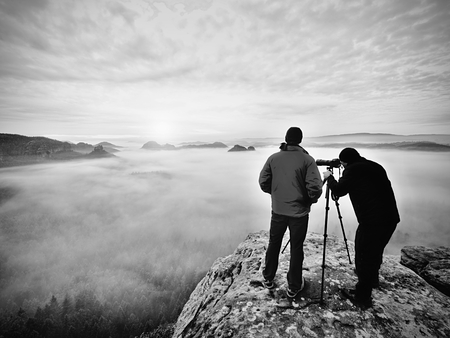 Silhouettes of man photographers. Men on mountain. Peak  with two men taking photos in autumn morning sunrise Фото со стока