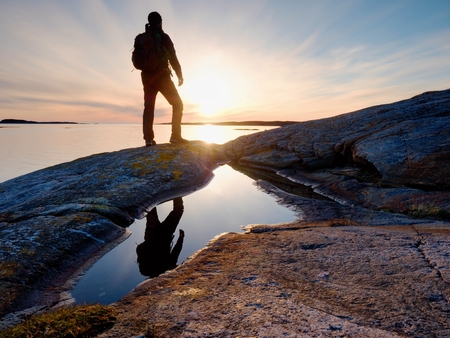 Tall backpacker watch clear sunny spring daybreak over sea. Hiker with backpack stand on rocky shore and his figure is mirrored in water pool.  Hiker enjoy breathtaking sunrise.  Hiking ambition.
