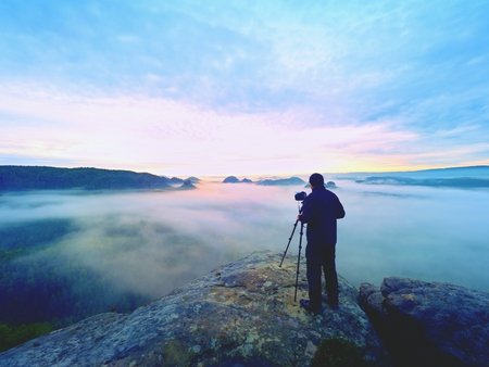 Photographer framing picture with eye on viewfinder. Photo enthusiast  enjoy work of fall nature on rocky summit. Dreamy landscape, misty sunrise in a beautiful valley below Stok Fotoğraf - 90864982