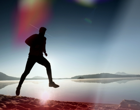 Leakage of light in the lens. Damaged photo effect. Handsome slim  man running on the beach. Exercising  silhouette against to morning Sun.