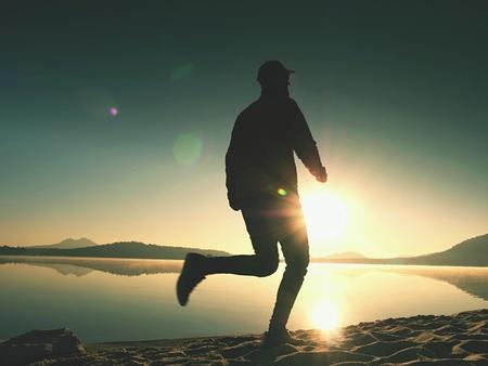Exercising on the lake beach at sunset, big sun at horizon Stock Photo