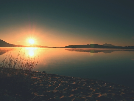 Abandoned sandy beach at lake, clear sky before  sunset,sun rays at horizon  and reflections in water level Stock Photo